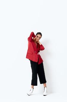 頭の後ろで手をつないでポーズをとって赤いジャケットの女性