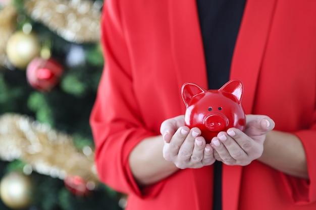 Женщина в красной куртке держит копилку на фоне елки, куда вкладывать деньги