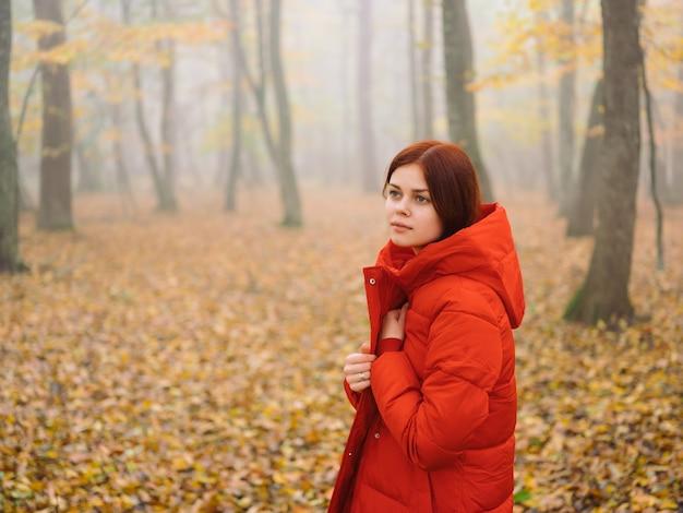 秋の森の霧の自然の新鮮な空気の赤いジャケットの女性