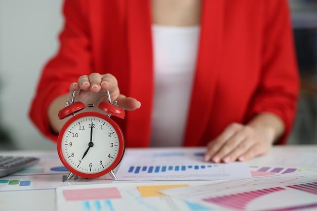 Женщина в красной куртке выключает будильник на столе крупным планом