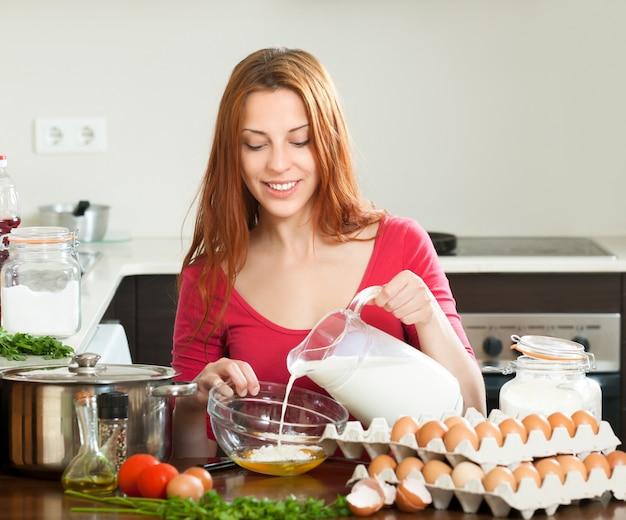 Женщина в красном, делая тесто или омлет на кухне