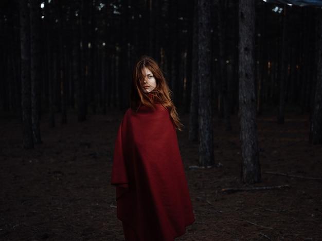 森の自然の中で赤い格子縞の女性は新鮮な空気を旅します。高品質の写真