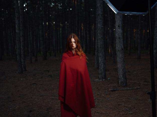 森の自然の中で赤い格子縞の女性は新鮮な空気を旅します
