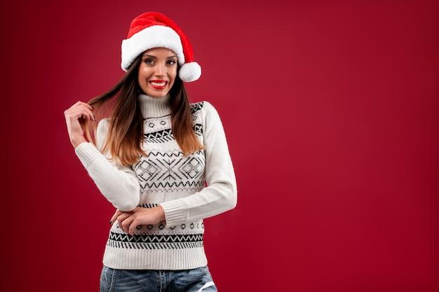 Женщина в красной шляпе санта на красном