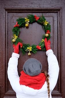 ドアにクリスマスリースをぶら下げて赤いスカーフと白いジャケットの女性