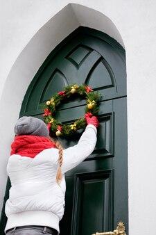 緑のドアにクリスマスリースをぶら下げて赤いスカーフと白いジャケットの女性