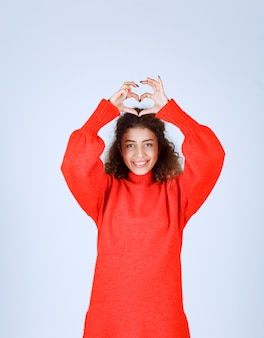 Женщина в красной рубашке дует любовь к своей толпе.