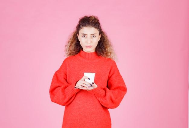 일회용 커피 컵을 들고 빨간색 셔츠에 여자.
