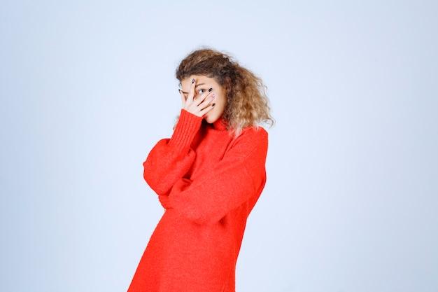 Женщина в красной рубашке, глядя сквозь пальцы и смеясь.