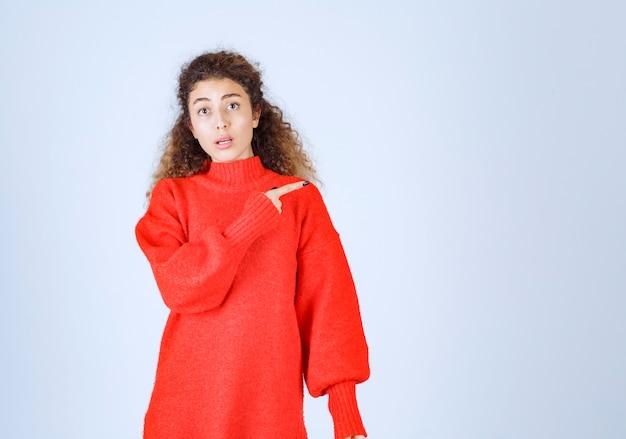 Женщина в красной рубашке, указывая на кого-то или куда-то с эмоциональным лицом на синем.