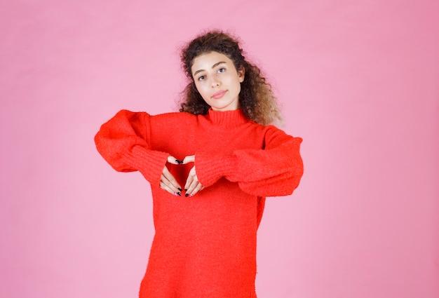 Женщина в красной рубашке, показывая знак сердца.