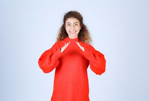 Женщина в красной рубашке, показывая знак крыши.