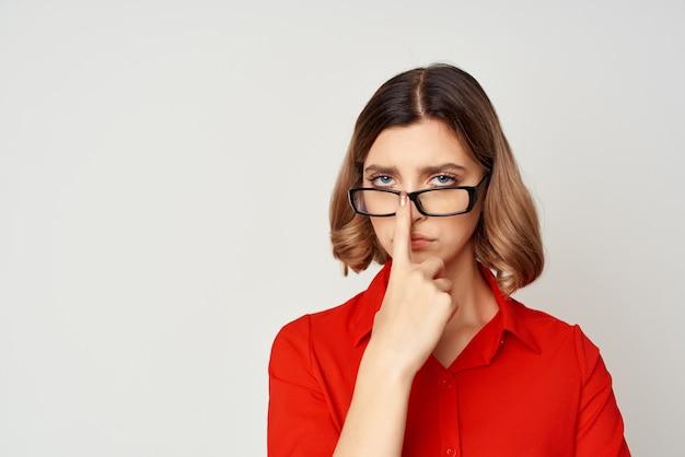 眼鏡マネージャーの仕事場を着ている赤いシャツの女性