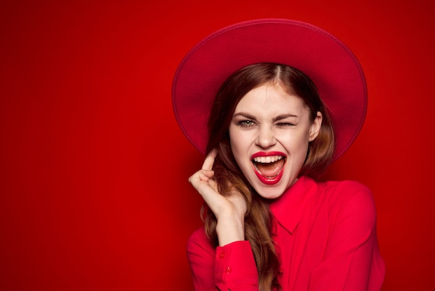 明るい化粧と彼女の頭の感情のファッションスタイルの帽子と赤いシャツの女性。