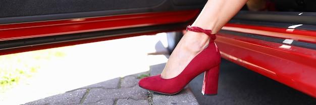 赤い靴を履いた女性が車のクローズアップから足を突き出しました