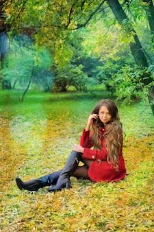 Женщина в красном, сидя в осеннем парке.
