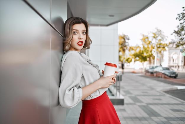 建物の近くで屋外でポーズをとってコーヒーの赤いスカートカップの女性