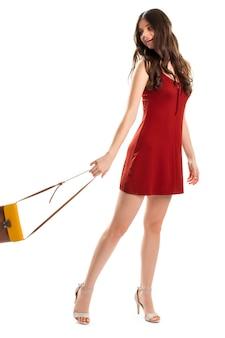 빨간 민소매 드레스를 입은 여자. 소녀는 스트랩이 달린 가방을 보유하고 있습니다. 열쇠 구멍 드레스와 디자이너 신발. 가벼움과 매력.