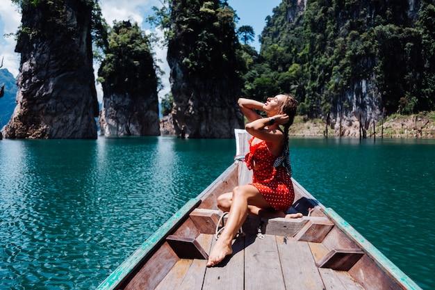 休暇中のタイのアジアのボートに乗って赤い夏のドレスを着た女性、タイを旅する