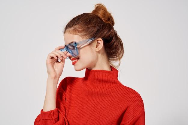 赤いセータージーンズ青い眼鏡の側面図の女性