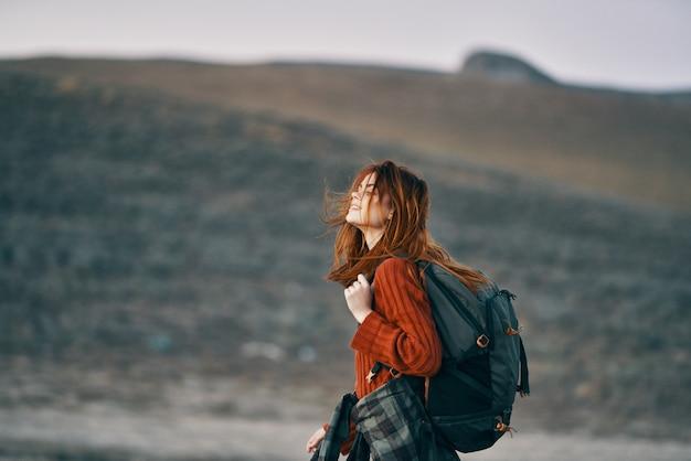 バックパックと赤いセーターの女性は山の自然を振り返る