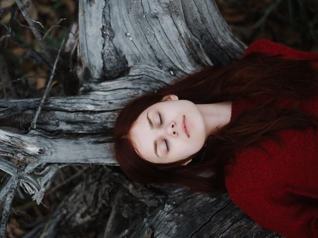 눈을 감고 빨간 스웨터를 입은 여자가 숲 속의 나무 근처 땅에 누워 있다