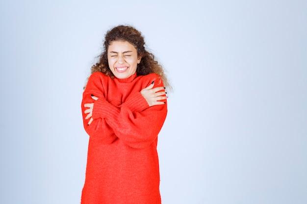寒さを感じている赤いスウェットシャツの女性。