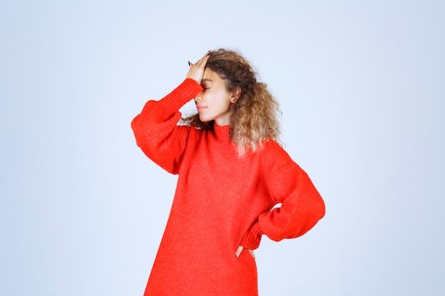 빨간색 셔츠에 여자는 피곤하고 졸려 보인다.