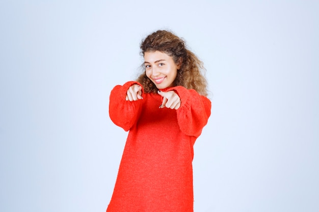前方の誰かを指している赤いスウェットシャツの女性。