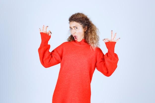 즐거움 기호를 보여주는 빨간색 셔츠에 여자입니다.