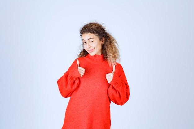 Женщина в красной толстовке, показывая знак удовольствия.