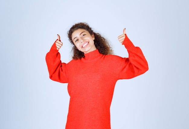 楽しみのサインを示す赤いスウェットシャツの女性。