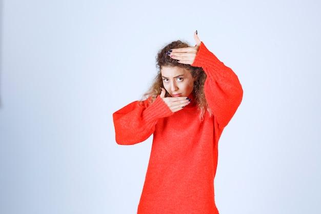 写真撮影のサインを示す赤いスウェットシャツの女性。