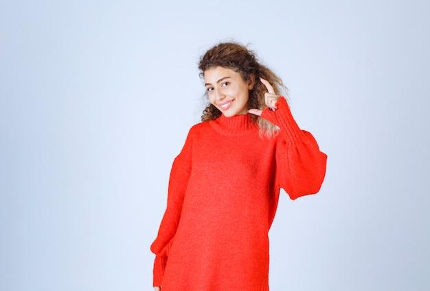 제품의 예상 금액 또는 크기를 보여주는 빨간색 셔츠를 입은 여성.