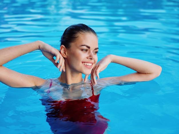 プールの自然の中で赤い水着の女性は、贅沢をクローズアップします。高品質の写真
