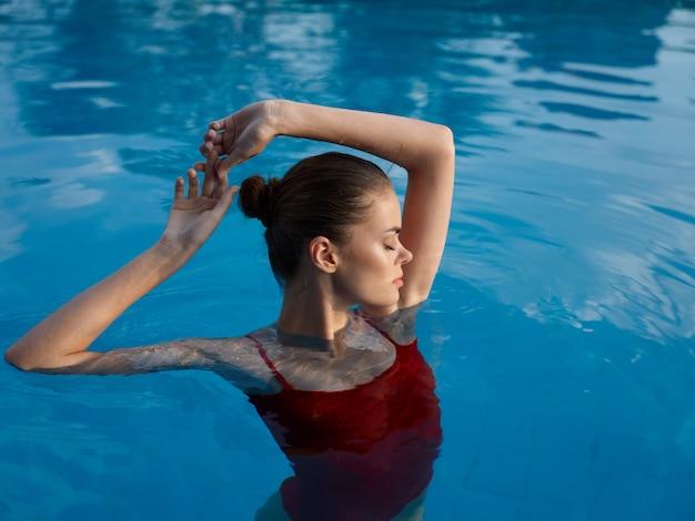 수영장에서 빨간 수영복을 입은 여자는 눈을 감고 손으로 제스처를 취합니다.