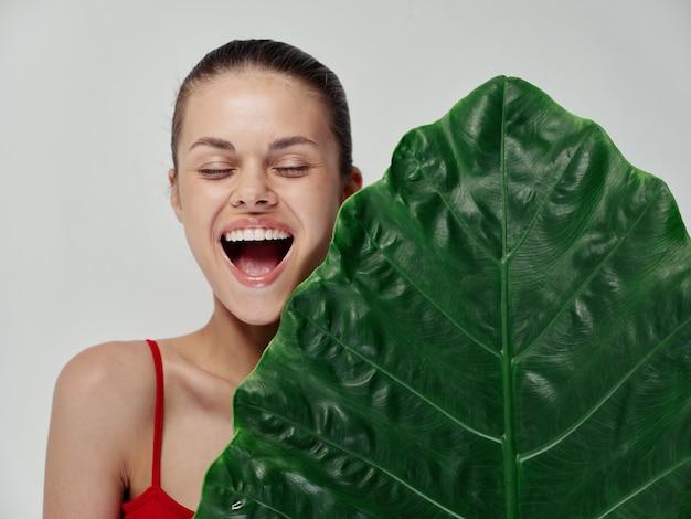 大きく開いた口と緑の葉のヤシの木のきれいな肌で笑っている赤い水着の女性