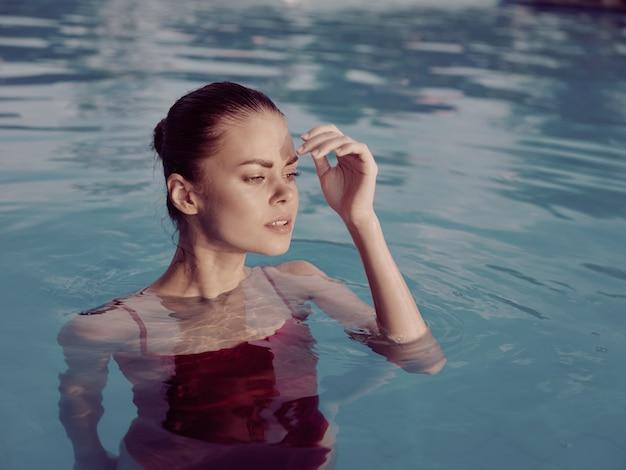 プールの贅沢な自然の中で泳ぐ赤い水着の女性