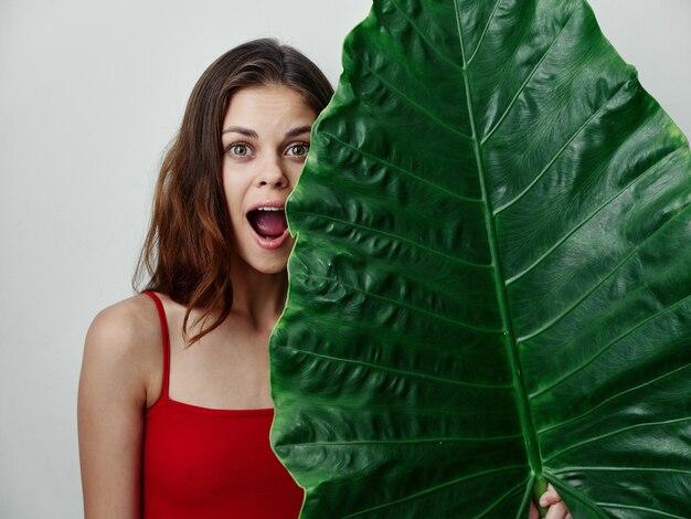 開いた口のヤシの葉のトリミングされたビューと赤い水着の女性
