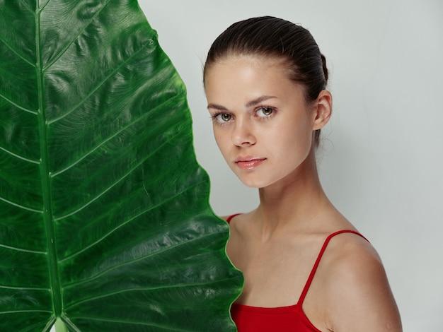 ヤシの葉のトリミングされたビュー明るい背景を持つ赤い水着の女性