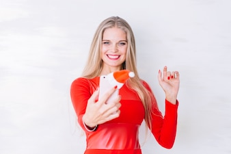 Woman in red taking selfie with phone