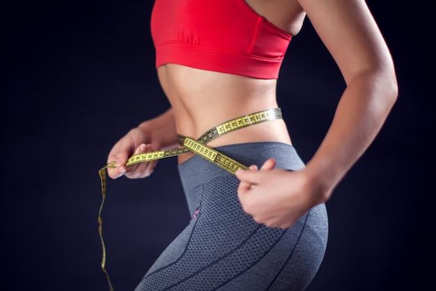 メーターで腰を測定する赤いトップの女性。スポーツ、ライフスタイル、健康の概念