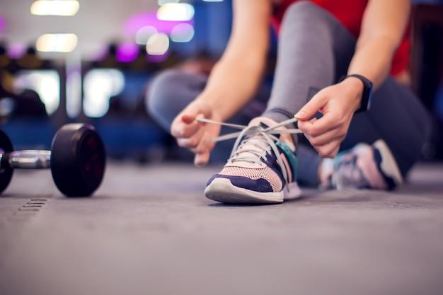 Женщина в красном топе с короткими светлыми волосами завязывает шнурки перед тренировкой в тренажерном зале. люди, фитнес и концепция стиля жизни