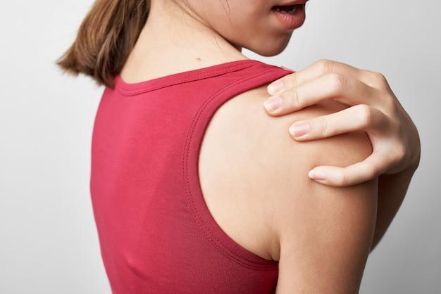 肩の健康問題関節炎治療の赤いtシャツの女性