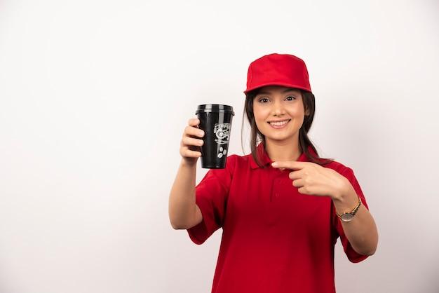 白い背景の上のコーヒーのカップを示す赤い制服を着た女性。