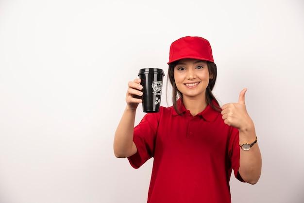Женщина в красной форме показывает чашку кофе на белом фоне.