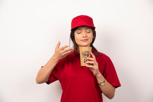 赤い制服を着た女性は、茶色のカップでアロマコーヒーを嗅ぎます。