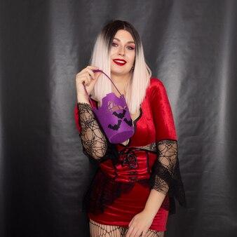 Женщина в красном платье вампира держит сумку для сладостей