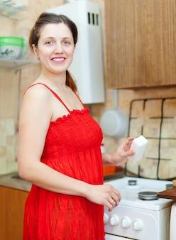 부엌에서 멜라민 스폰지와 함께 빨간색으로 여자