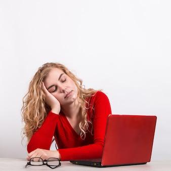Женщина в красном, работающая удаленно за компьютером на белом.